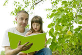 Father and daughter reading a book on nature — Stock Photo