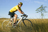 Young bicyclist in a yellow form on nature — Stock Photo