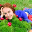 Gipsy girl in blue, lying on green grass with a flower — Stock Photo