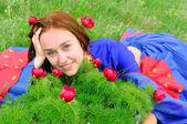 ジプシー青い服の少女、花と緑の草に横たわって — ストック写真
