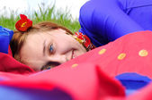 Gipsy girl in blue, lying on green grass — Stock Photo