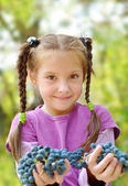 Girl gives bunches grapes — Stock Photo