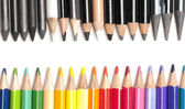 Colored pencils opposing black and white pencils — Stock Photo