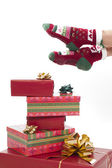Female legs in christmas stockings isolated on white. Gifts on t — Stock Photo