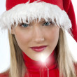 Beautiful young woman in santa's hat holding a red candle - Stock Photo
