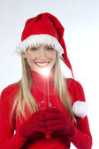 Beautiful young woman in santa's hat holding a red candle — Stock Photo