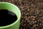 Coffee cup on coffee beans — Stock Photo