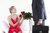 Receiving red rosesHappy and surprised woman receiving red roses — Stock Photo