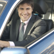 Smiling businessman driving car — Stock Photo