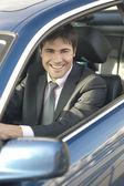 Smiling businessman driving car — Stock Photo