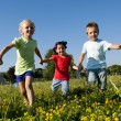 Three children running holding hands — Stock Photo