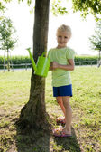 Little girl watering tree — Stock Photo