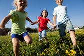 Three children running holding hands — Stock Photo
