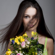Beauty with a bunch of flowers — Stock Photo