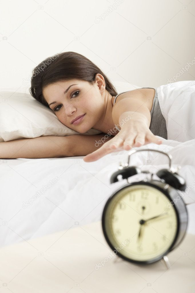 Young woman waking up in the morning , trying to put off an alarm clock — Stock Photo #4171935