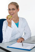 Beautiful female doctor eating an apple while working in her off — Stock Photo