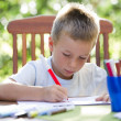 Little boy coloring outside - Stock Photo