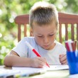 Stock Photo: Little boy coloring outside