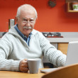 Senior man speaking through webcam — Stock Photo