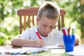 Little boy coloring outside — Stock Photo