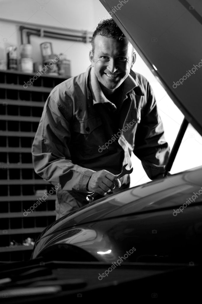 Smiling mechanic controlling car engine — Stock Photo #4210439