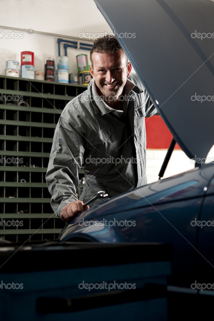 Smiling mechanic controlling car engine  Foto Stock #4210526