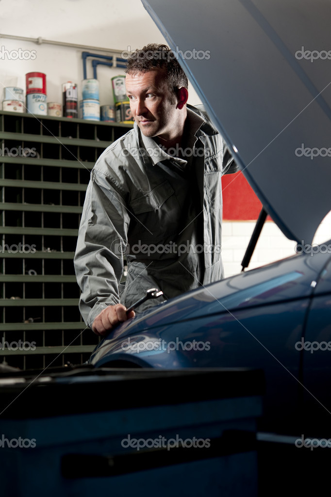 Smiling mechanic controlling car engine — Stock Photo #4210563