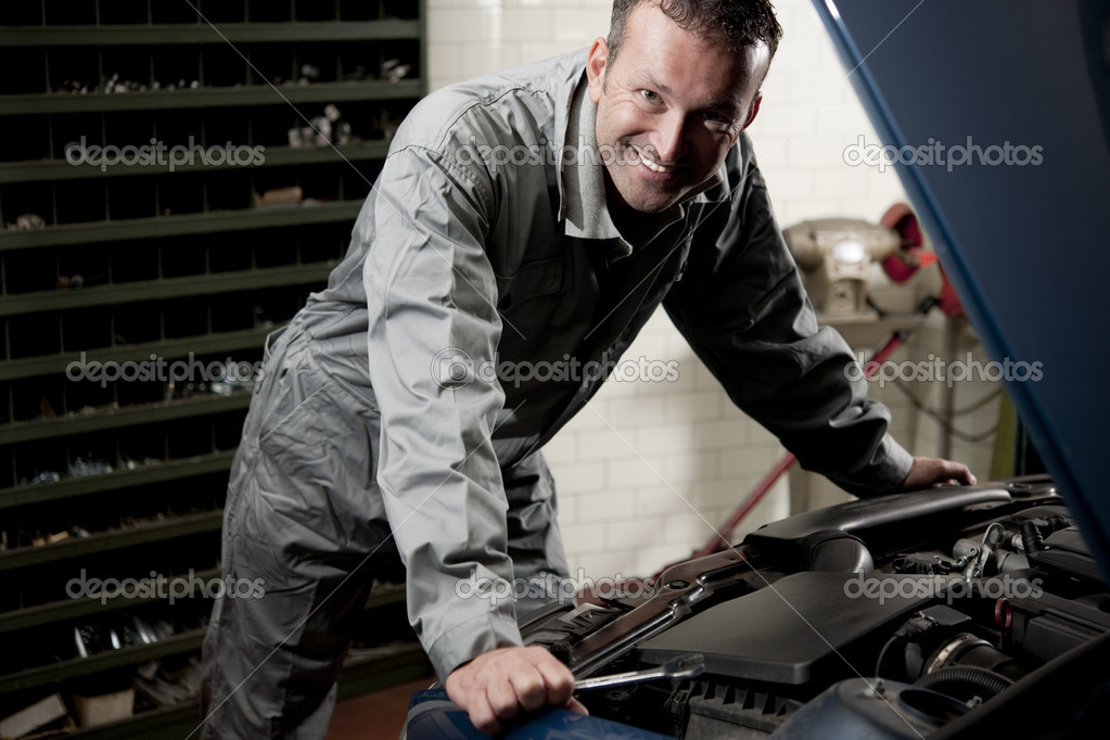 Smiling mechanic controlling car engine  Stock Photo #4210645