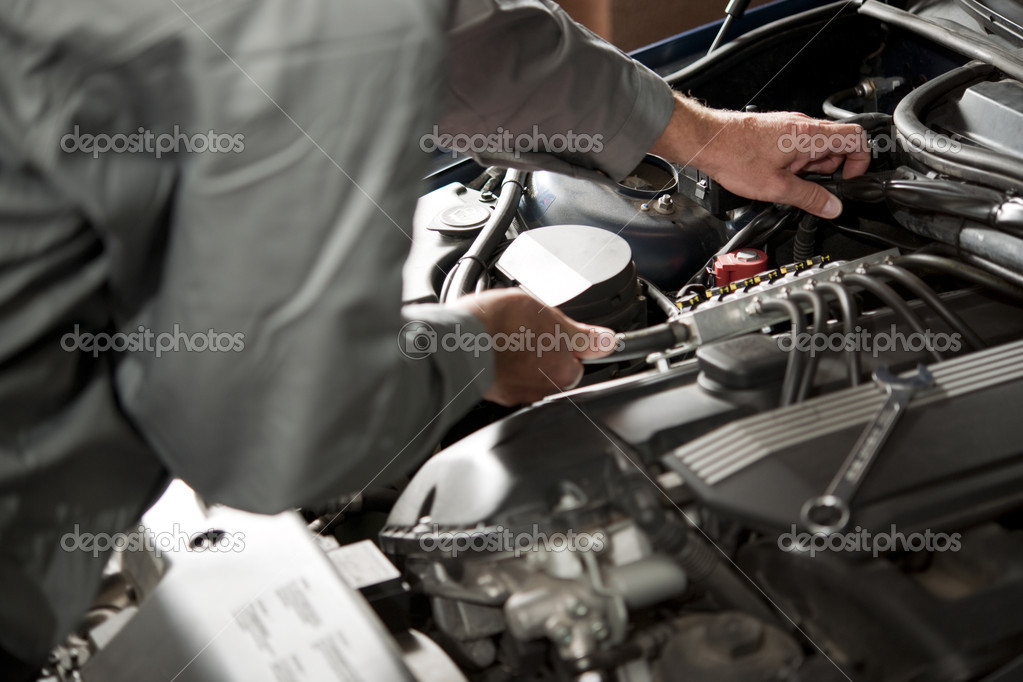 Male hand repairing car engine — Stock Photo #4210751