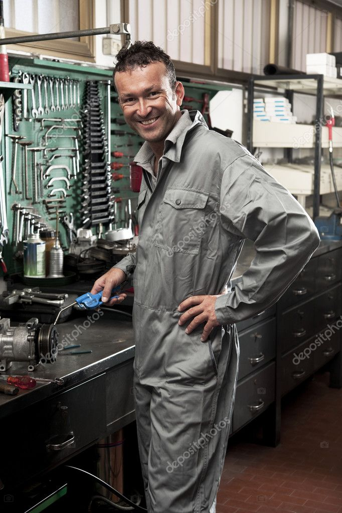 Close-up of a smiling mechanic inside his auto repair shop — Stock Photo #4210872