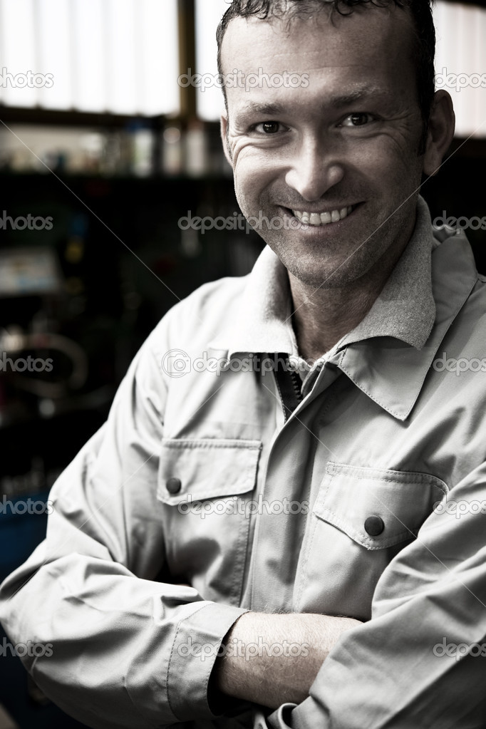 Close-up of a smiling mechanic inside his auto repair shop  Stock Photo #4210963