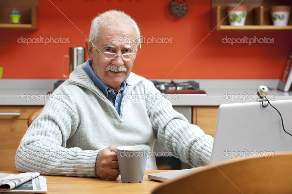 Senior man speaking through webcam in his kitchen — Stock Photo #4216035