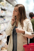 Young woman at supermarket — Stockfoto