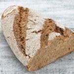 Wholegrain bread on wooden table, healty food — Stock Photo