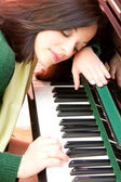 Portrait of a beautiful brunette and her piano — Stock Photo