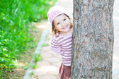 Little girl hiding behind a tree — Stock Photo