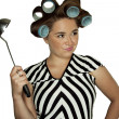 Housewife in hair rollers with a ladle - Stock Photo