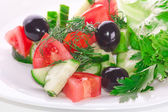 Greek salad from tomatoes, olives and a cucumber with greens — Stock Photo