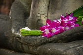 Sitting Buddha in meditation position, with fresh Orchid flowers — Stock Photo