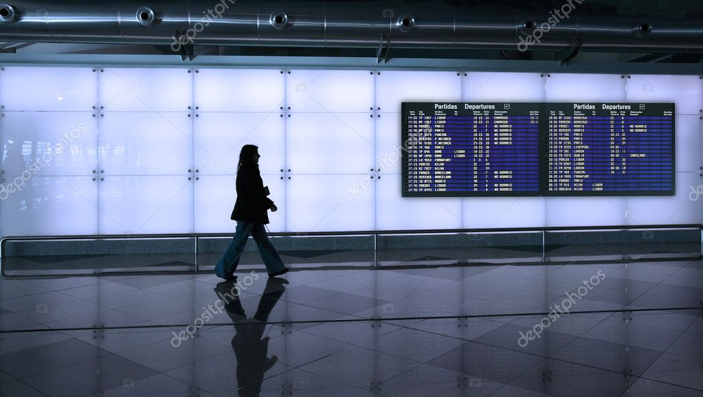 Woman walking in the airport with information board — Stock Photo #3641297