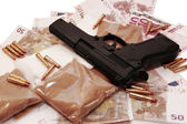 Drugs vice gun and money — Stock Photo