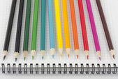 Multicolored pencils on opened spiral notebook — Stok fotoğraf