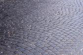 Der straße, mit schwarzen steinen bedeckt — Stockfoto