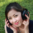 Beautiful girl listening music in the park — Stock Photo