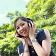 Beautiful girl listening music in the park — Stock Photo #3886430
