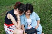 Dos hermosas chicas con el ordenador portátil sobre fondo natural — Foto de Stock