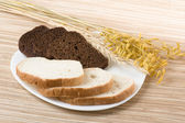 Cut black and a white loaf on a plate — Stock Photo