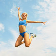 Stock Photo: Sportswomin jump against sky