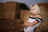 Girl leaning on hay — Stock Photo