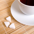 White sugar and cup coffee on bamboo mat — Stock Photo